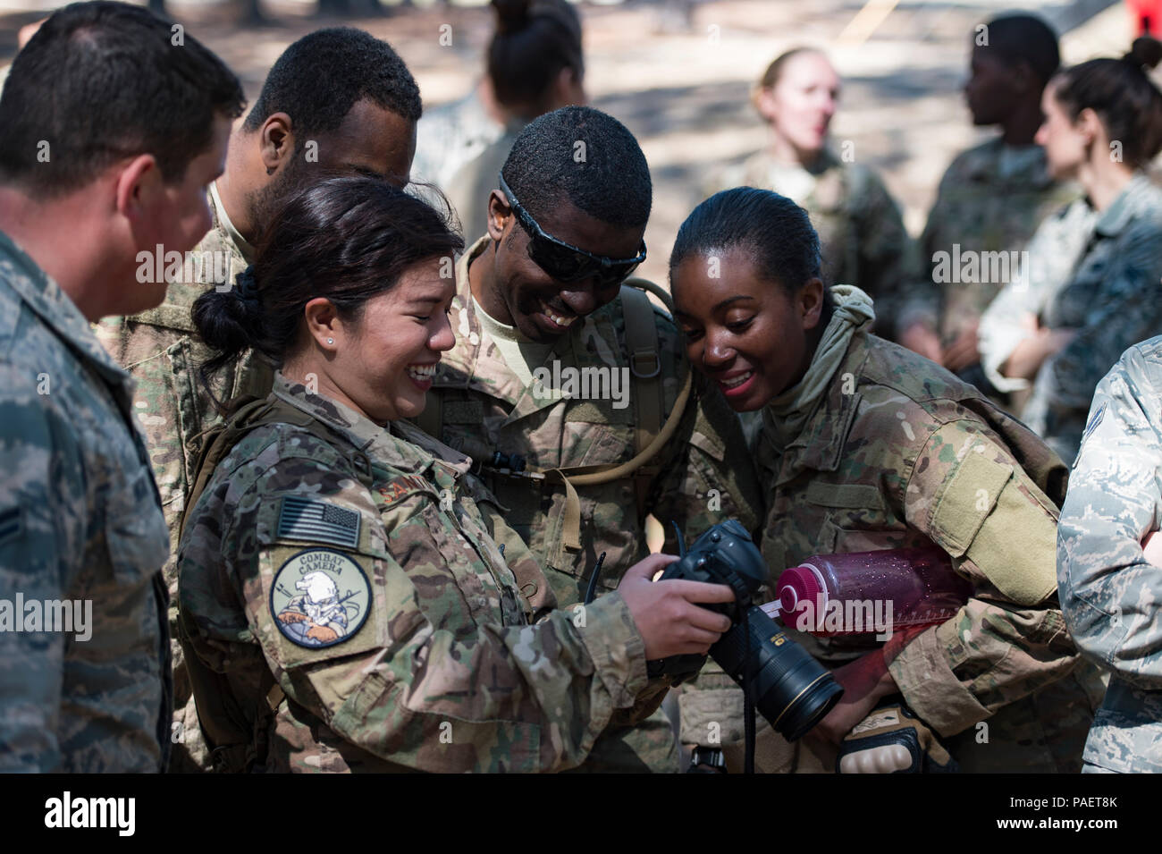 """First and 3rd Combat Camera Squadron airmen look at photos taken by U.S. Air Force Staff Sgt. Marianique Santos, 1st CTCS combat photojournalist, during exercise Scorpion Lens, March 6, 2016, at Fort Jackson, S.C. Exercise Scorpion Lens is an annual Ability To Survive and Operate training evolution mandated by Air Force 3N0XX Job Qualification Standards (3N0XX AFJQS).  Individuals are instructed using a """"crawl, walk, run"""" format of training. The purpose of the training is to provide refresher training to combat camera personnel of all ranks and skill levels in basic tactics, techniques, and pr Stock Photo"""