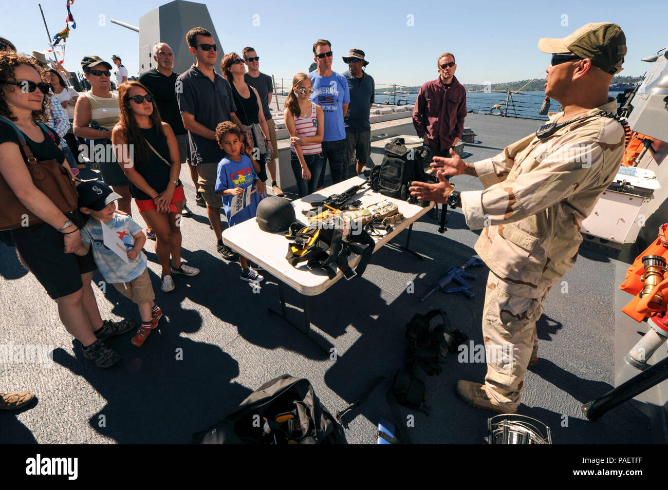 SEATTLE, Wash. (July 30, 2015) Damage Controlman 1st Class Benrichard Victorino, a Los Angeles native assigned to USS Gridley (DDG 101), presents equipment used in anti-terrorism force protection during ship tours on the Arleigh Burke-class guided missile destroyer for Seafair Fleet Week. Seafair Fleet Week is an annual celebration of the sea services wherein Sailors, Marines and Coast Guardsmen from visiting U.S. Navy and Coast Guard ships and ships from Canada make the city a port of call. Stock Photo