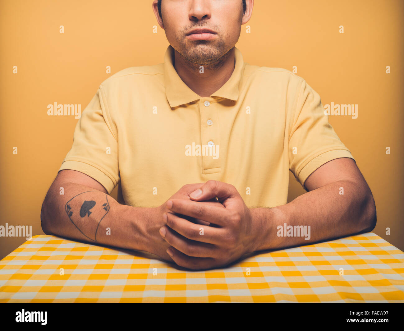 Young man against yellow backdrop is contemplating - Stock Image
