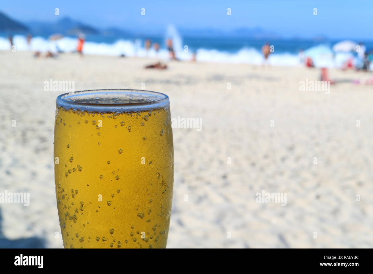 One big glass of cold draft beer with Blurred Copacabana beach full of people in background, Rio de Janeiro, Brazil - Stock Image