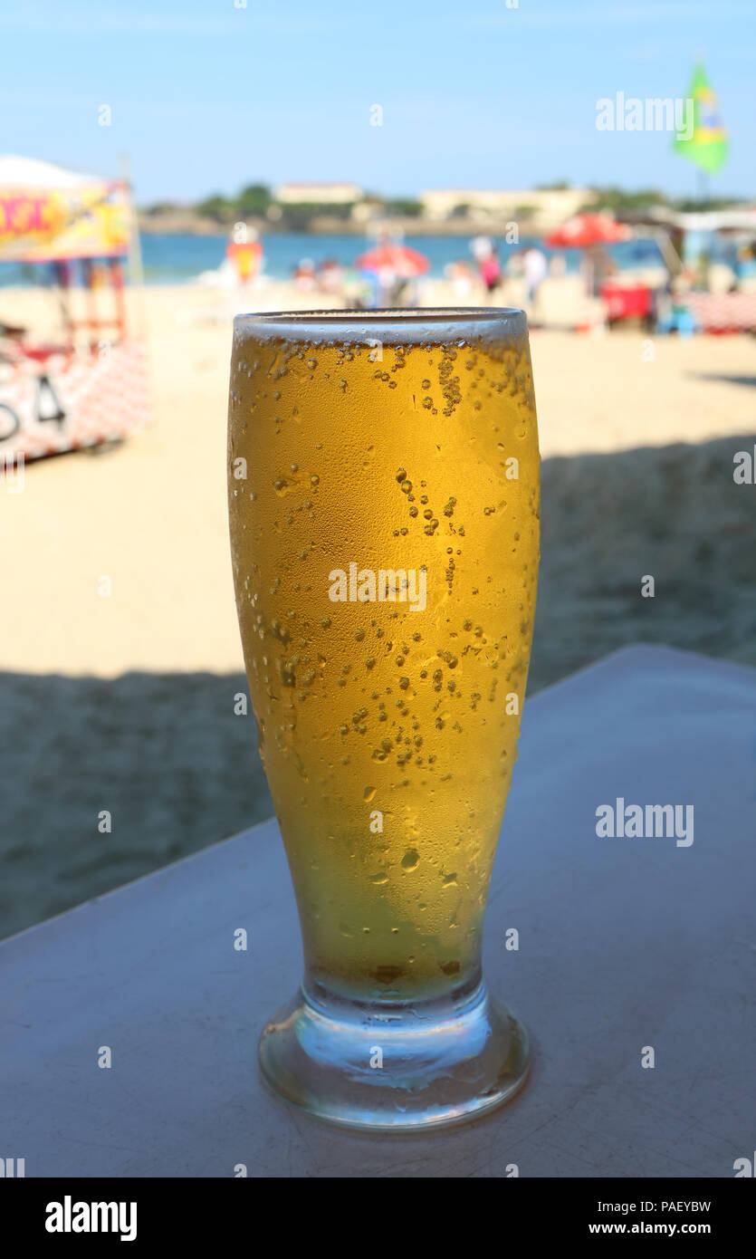 Front view of a glass of cold draft beer at sunny Copacabana beach in Rio de Janeiro, Brazil - Stock Image