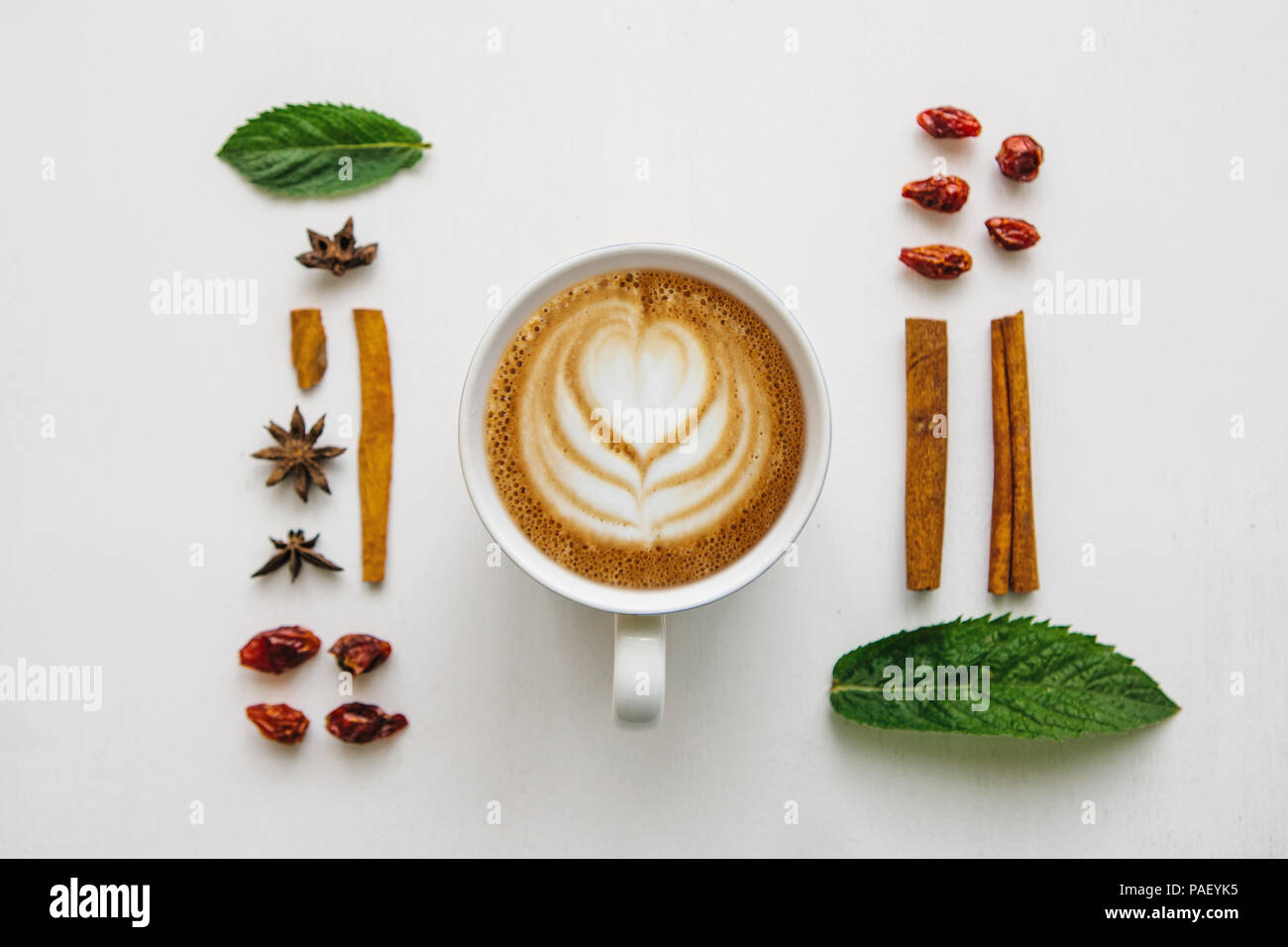 Flat lay a cup of delicious fresh cappuccino on a white surface and various ingredients. - Stock Image