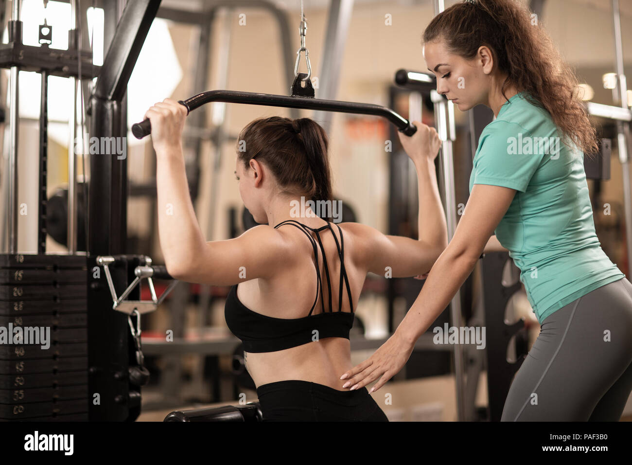Personal trainer helping girl making excercise in gym - Stock Image