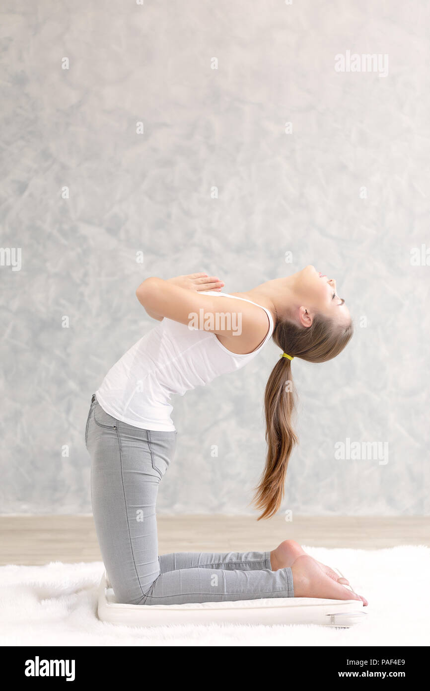 Young caucasian very attractive woman practicing yoga, sitting in Padmasana doing yoga exercise or Lotus pose or namaste pose. Working out on her bed. - Stock Image