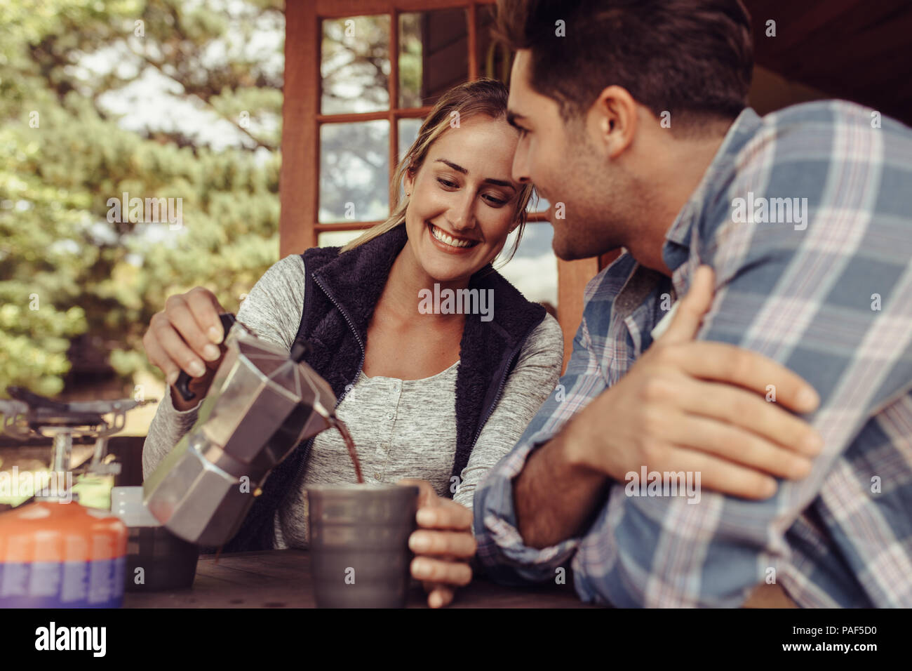 Happy young woman serving coffee to her boyfriend. Couple having coffee in the morning. Woman pouring coffee in the cup of her boyfriend. - Stock Image