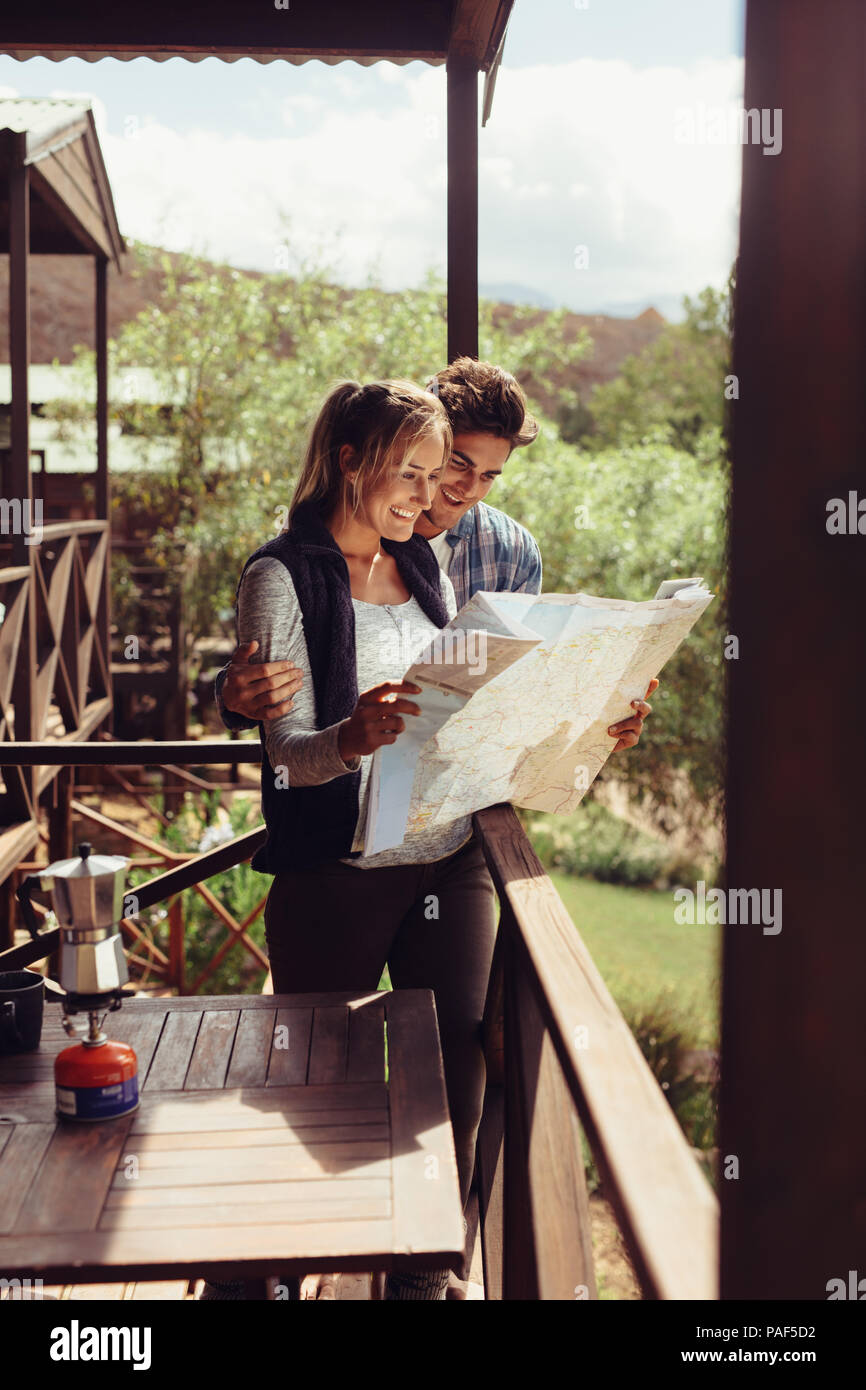 Couple standing in their hotel room balcony and looking at map. Man and woman reading map for finding nearest tourist attraction. Stock Photo