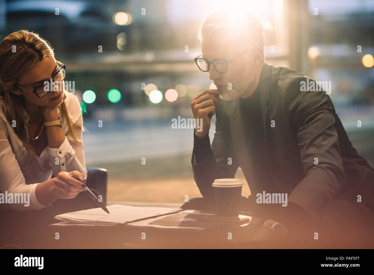 Two business people discussing over some paperwork while in office lobby. Business people working together in office. - Stock Image