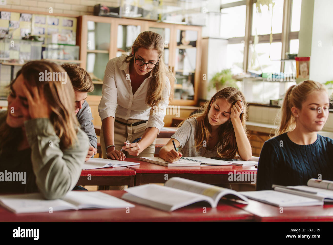 Group of university students attending lecture on campus with teacher helping in studies. - Stock Image