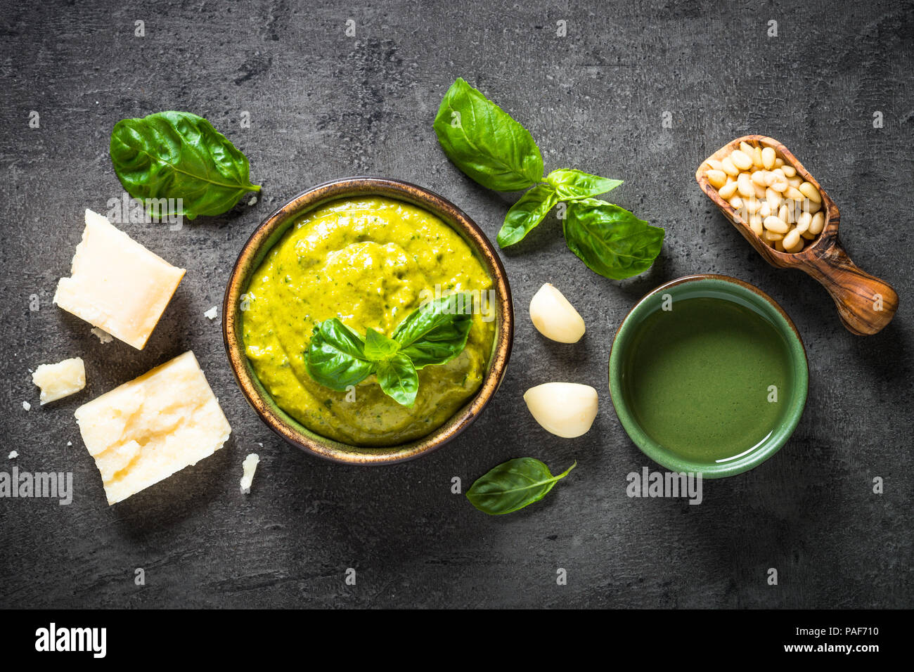Pesto sauce with ingredients on black slate table.  - Stock Image