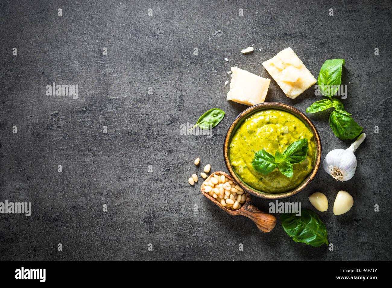 Pesto sauce with ingredients on dark stone table.  - Stock Image