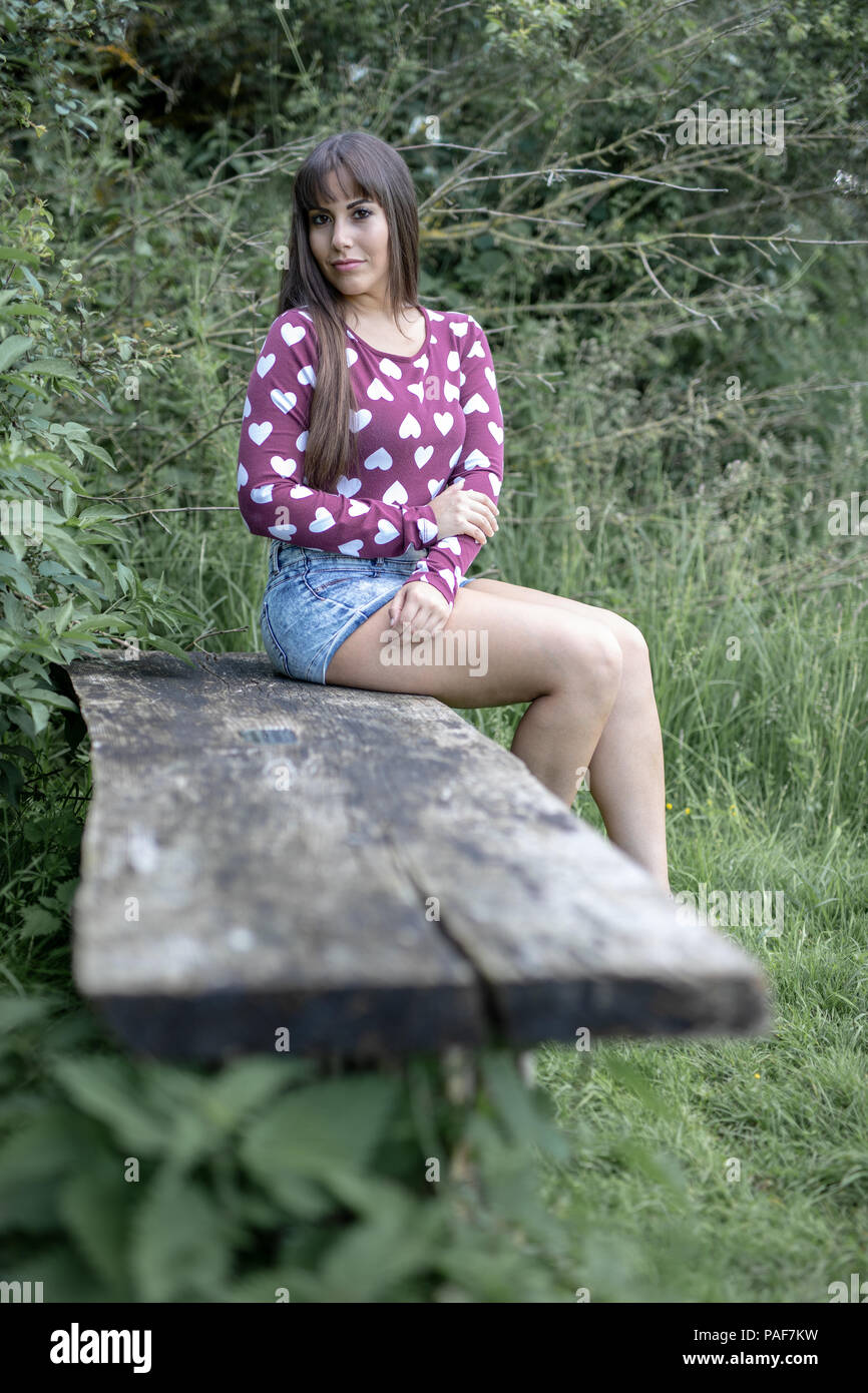 Spanish American female sitting on a wooden bench in the Cambridgeshire countrside.  Wearing a plum coloured top with hearts and blue denim shorts. - Stock Image