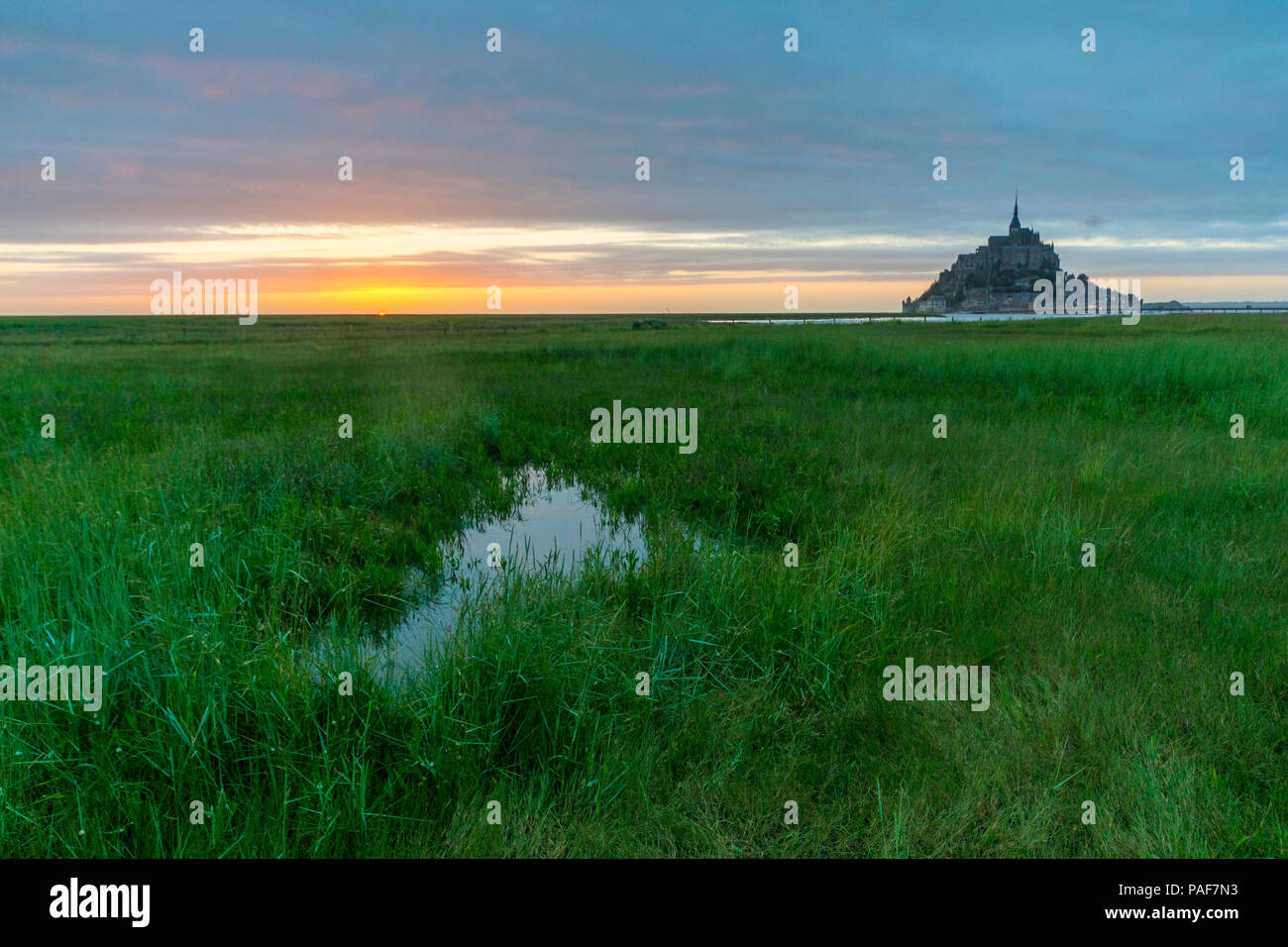 Mont st. Michel, Normandy, France. A half-flooded field in front of the famous island and abbey at dusk Stock Photo