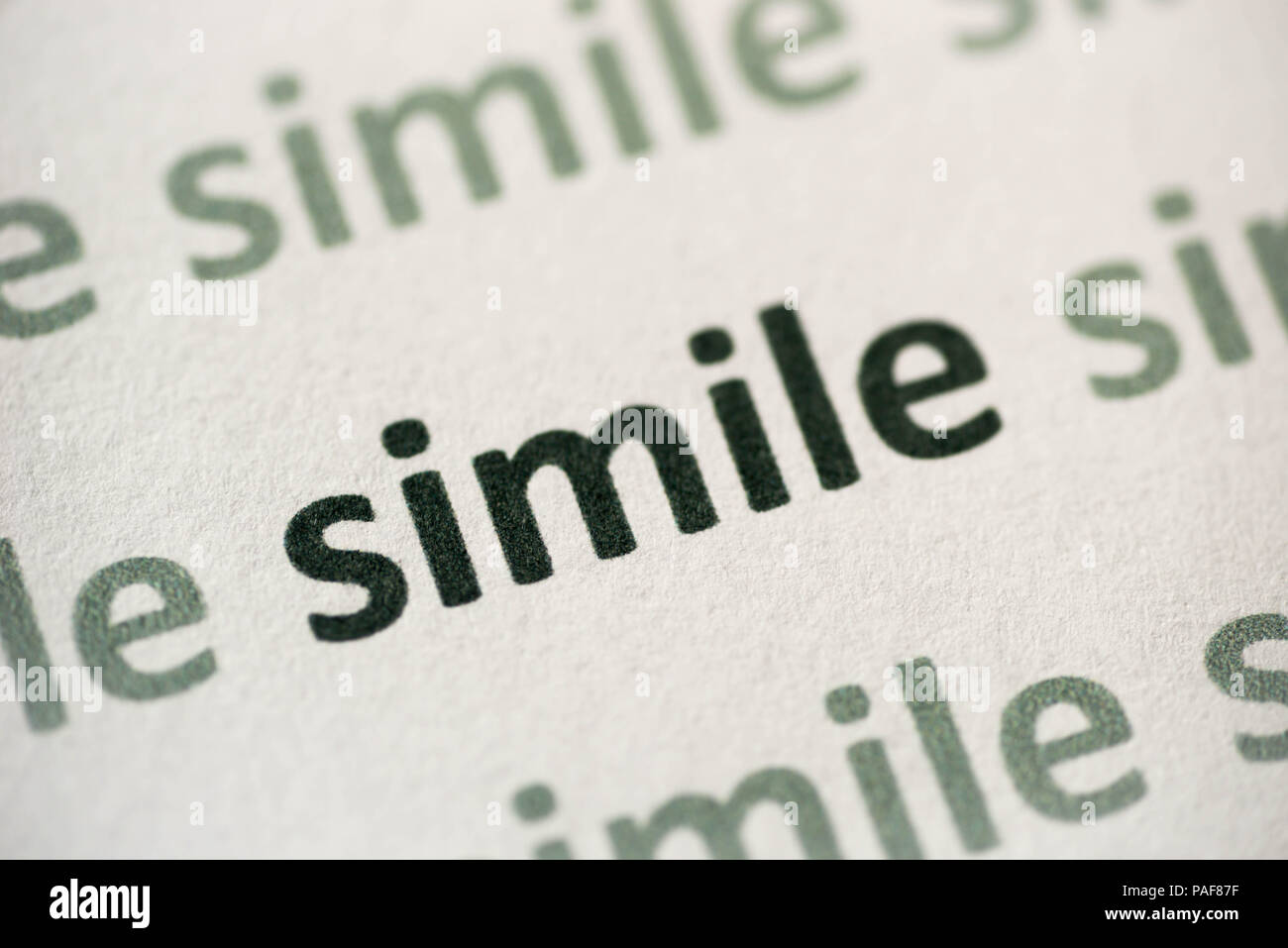 word similie printed on white paper macro - Stock Image