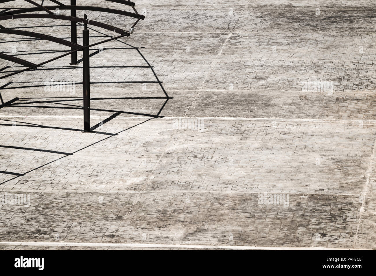 grey tiled floor with shadows from a canopy - Stock Image