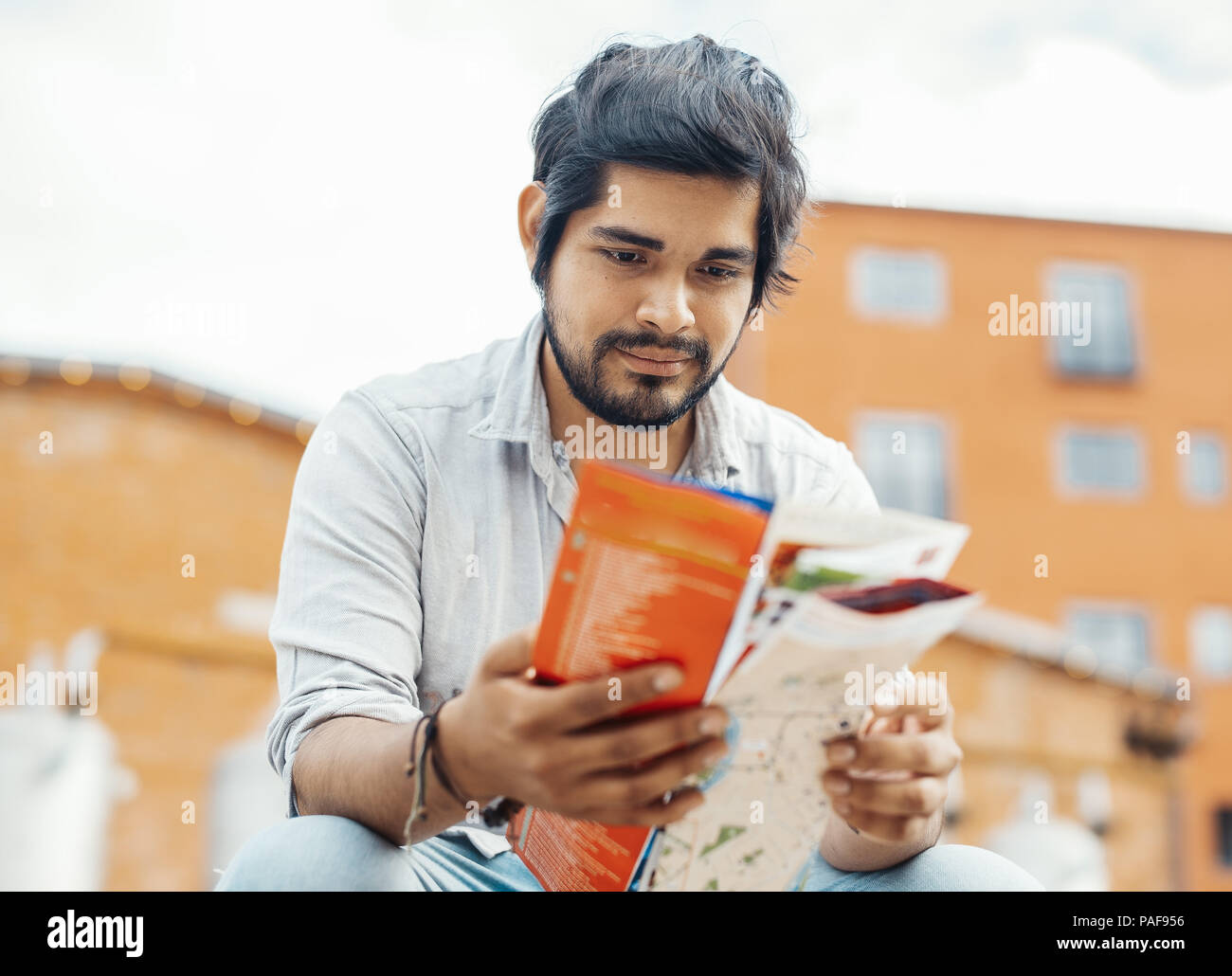 Attractive latin man looking at the map. - Stock Image