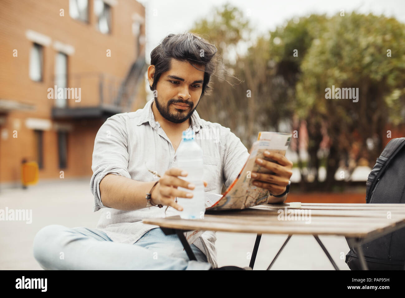 Attractive man sitting at street cafe, looking at the map and holding bottle. - Stock Image
