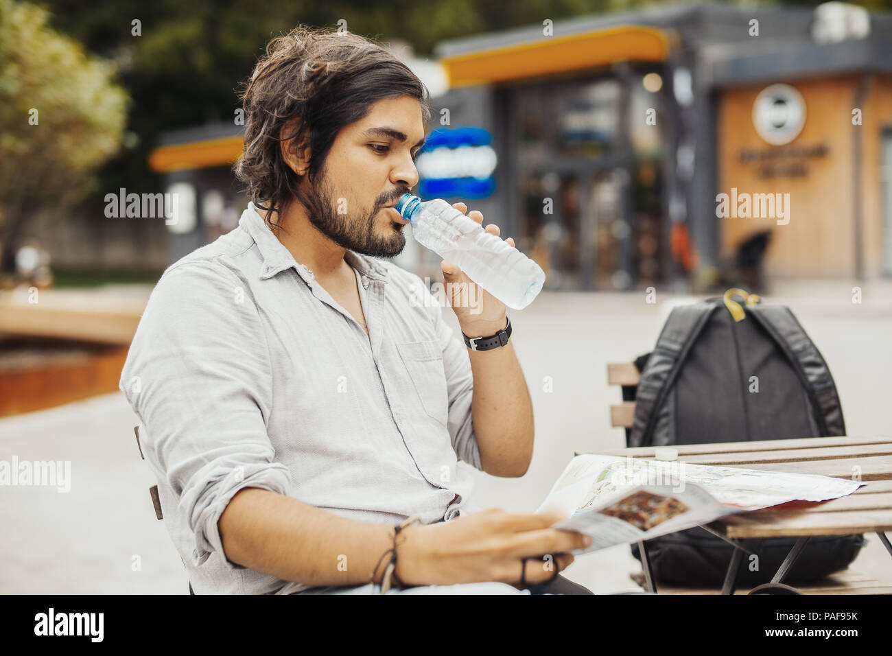 Attractive man sitting at street cafe, looking at the map and drinking water. - Stock Image