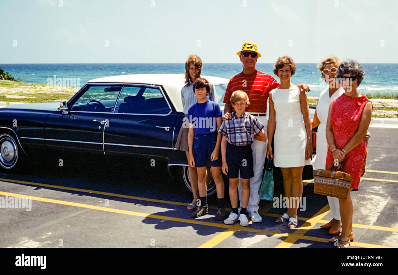 American family group portrait with three generations with children, mother, Aunt and grandparents, standing by 1969 Cadillac Sedan DeVille car parked next to beach and coast, Boca Raton, Florida, USA.  Digital conversion of historical photo taken in 1970 - Stock Image