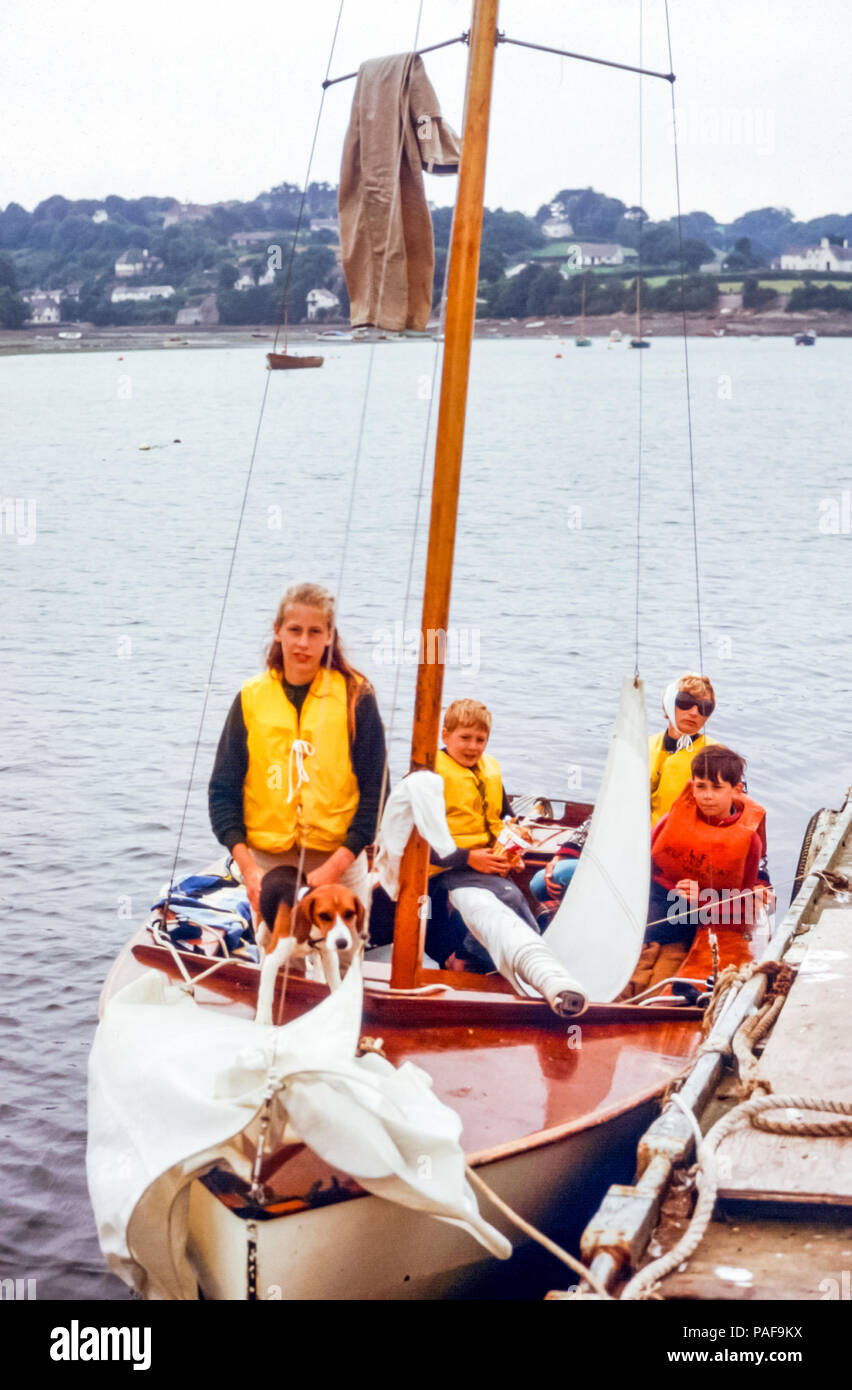 1960s family in small sailing boat with pet dog in Helford River, Cornwall, England, UK. Mother wearing sunglasses and head scarf, with girl holding beagle dog and two young boys. They are wearing life vests. Digital conversion of historical photo taken in 1968 - Stock Image
