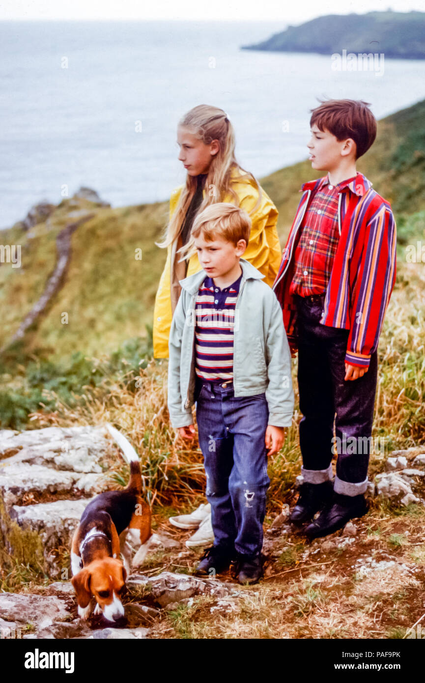 1960s children in family group of girl and two boys with pet Beagle dog standing on footpath above Cornish coastline, Cornwall, England, UK. Digital conversion of historical photo taken in 1968 - Stock Image
