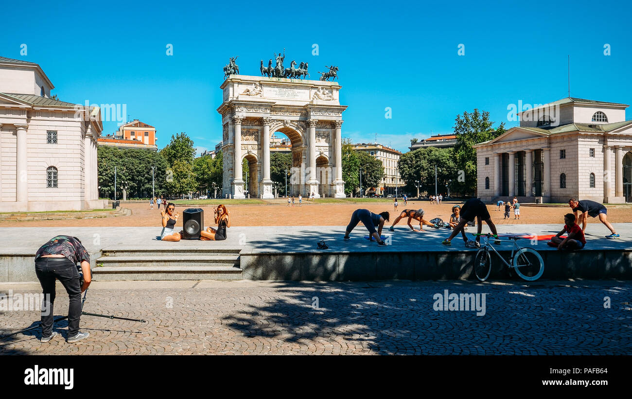 People exercise and socialise in front of Arco della Pace known as Arch of Peace in Milan, Italy, built as part of Foro Bonaparte to celebrate Napoleon's victories - Stock Image