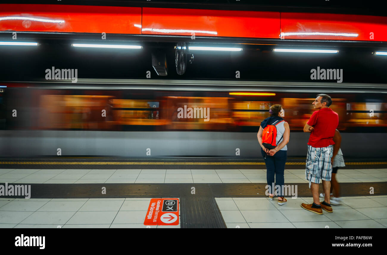 Fast moving purposely blurred train with passengers waiting at edge of platform at Milan's metro station - Stock Image