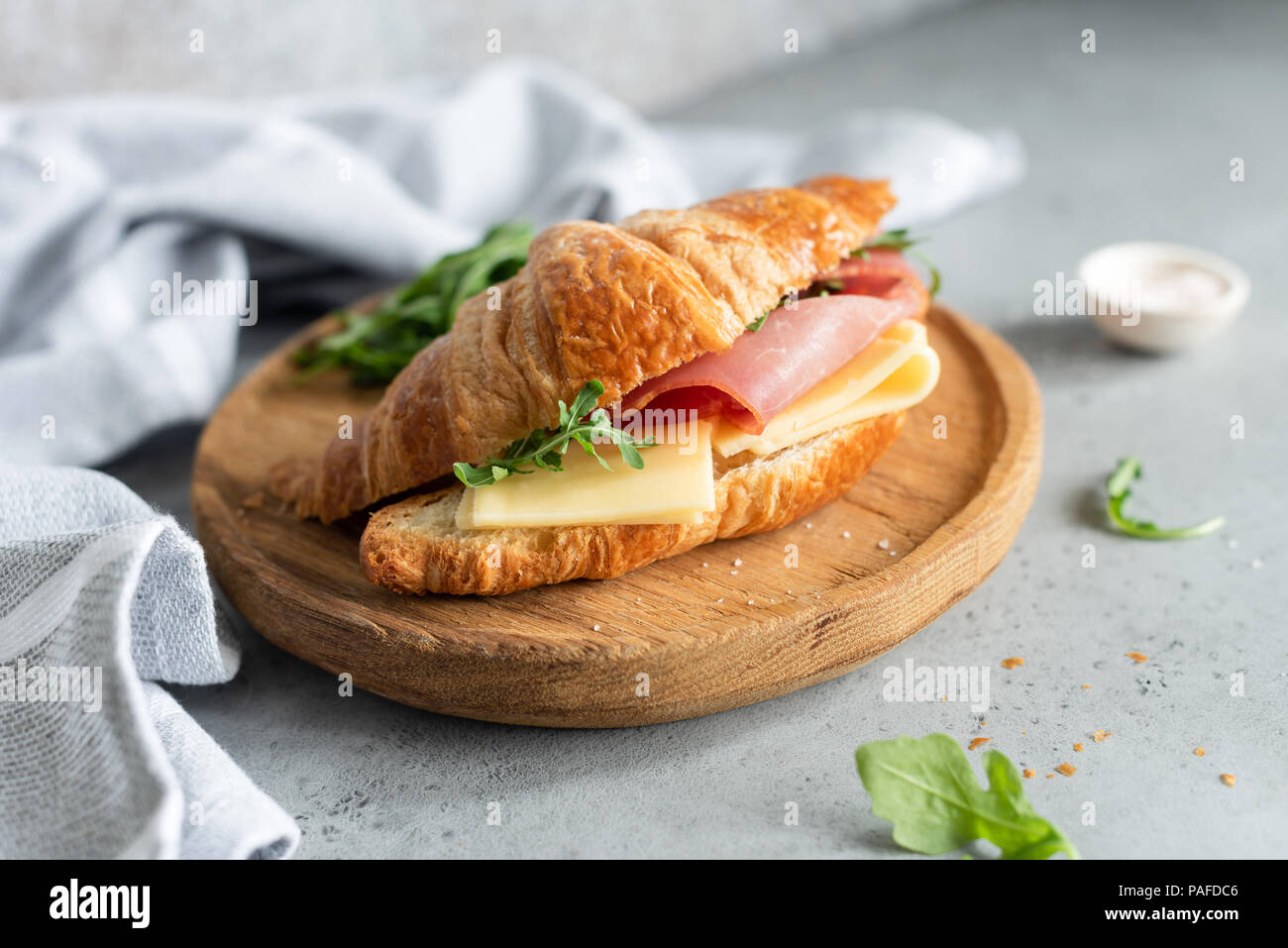 Sandwich with ham and cheese on croissant bun. Tasty croissant sandwich. Selective focus - Stock Image