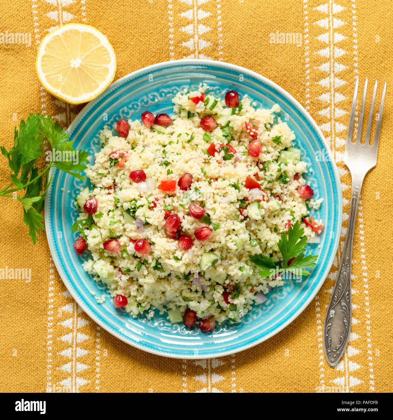 Couscous tabbouleh salad with pomegranate on blue teal plate over ethnic textile. Top view, square crop - Stock Image