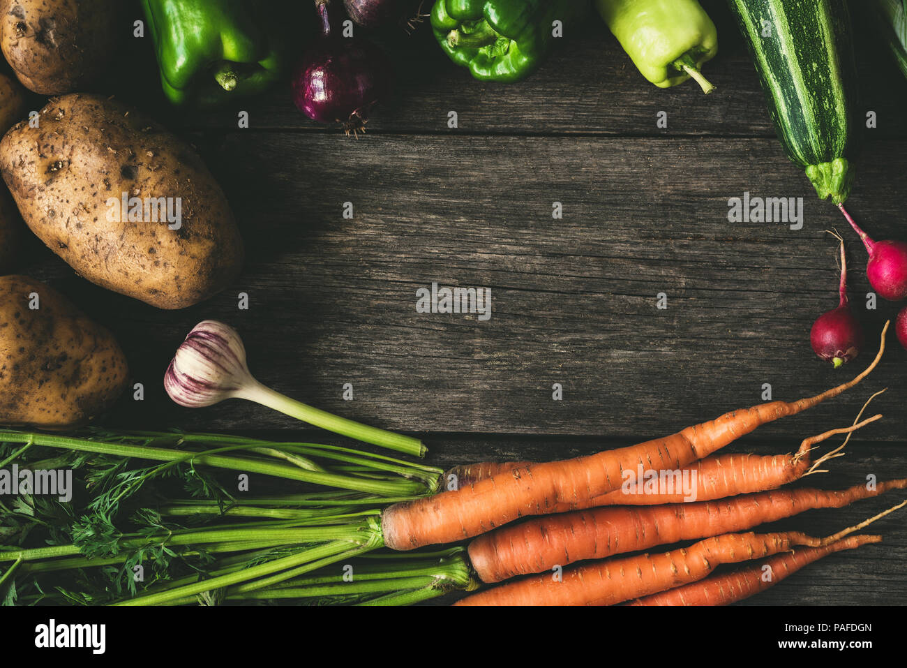 Vegetables on wood background, frame composition. Potatoes, carrots, garlic, peppers, zucchini and radishes on old wood table, copy space for text. Ag Stock Photo