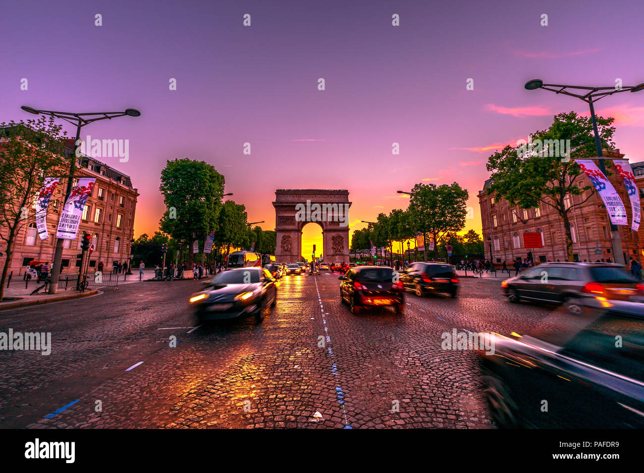 Paris, France - July 2, 2017: Avenue des Champs Elysees and iconic Arc de Triomphe at twilight with traffic street. Arch of Triumph in a colorful sunset sky. - Stock Image