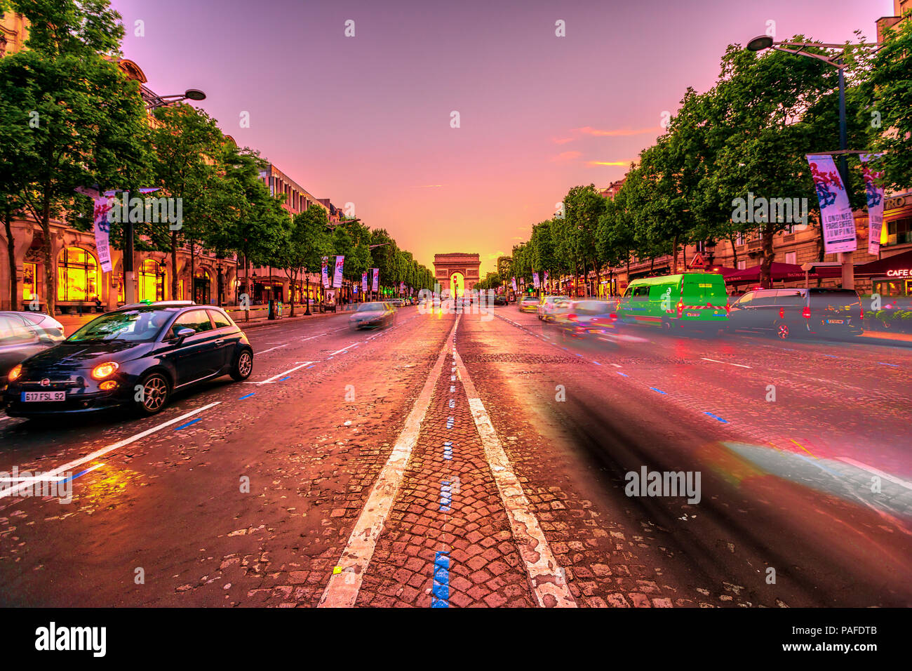 Paris, France - July 2, 2017: speed effect of the cars on the Champs Elysees with the iconic Arc de Triomphe in the distance at twilight. Arch of Triumph in a colorful sunset sky. - Stock Image