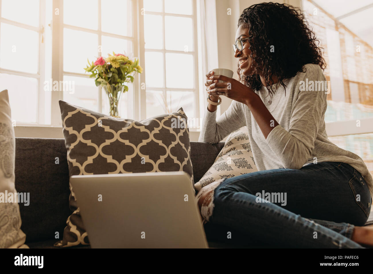 Businesswoman working on laptop computer sitting at home holding a coffee cup in hand. Smiling woman sitting on sofa at home and looking out of the wi - Stock Image