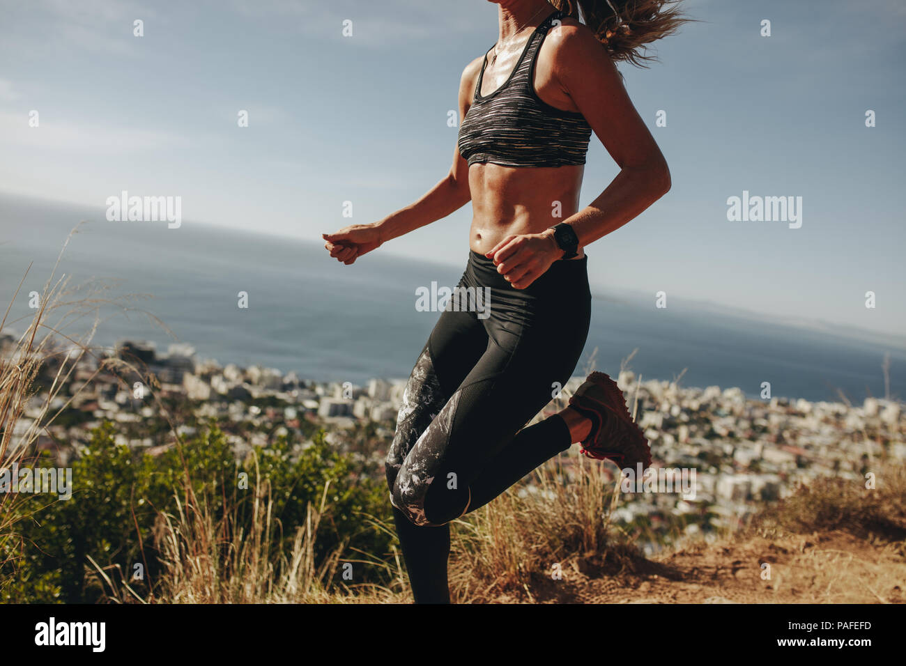 Healthy woman sprinting over mountain trail. Female doing running workout on path over hill. Cropped shot. - Stock Image