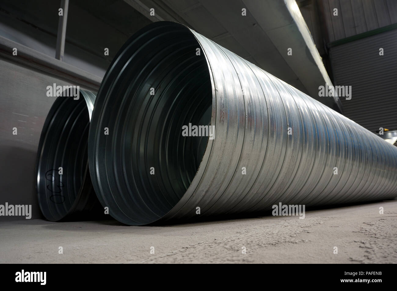 Galvanised steel ducting tubing for air extraction on the floor of a factory warehouse - Stock Image