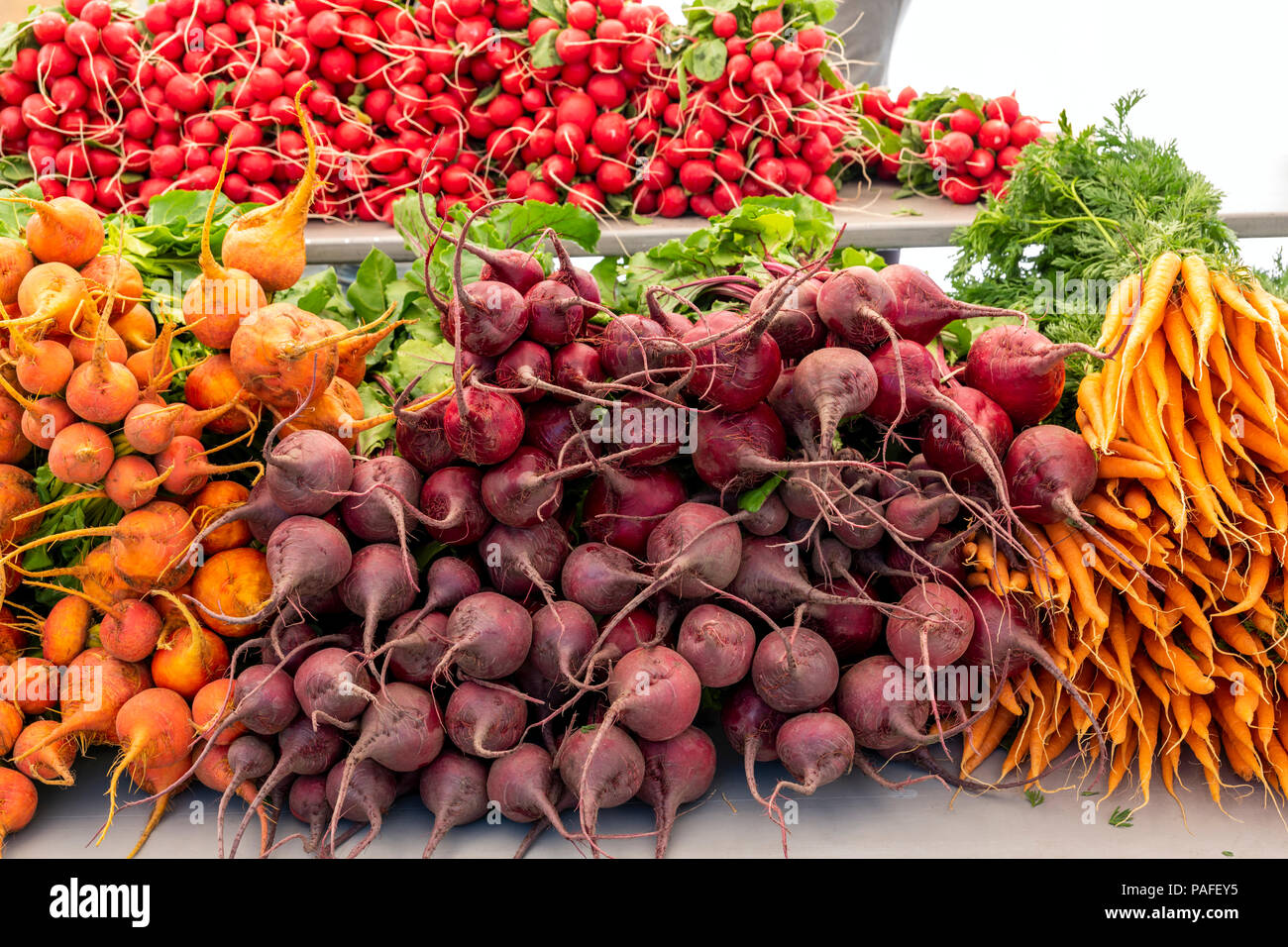 Vendors sell fresh vegetables, produce and other items at a seasonal farmers market in small mountain town of Salida, Colorado, USA - Stock Image