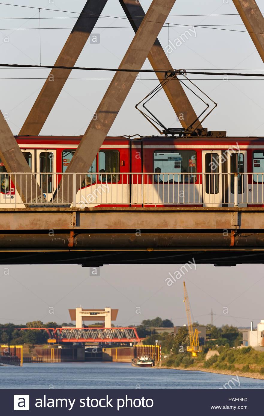Duisburg Meiderich truss bridge with tram streetcar crossing Rhine-Herne-Canal waterway lock sluice gate tower water traffic transport inland port - Stock Image