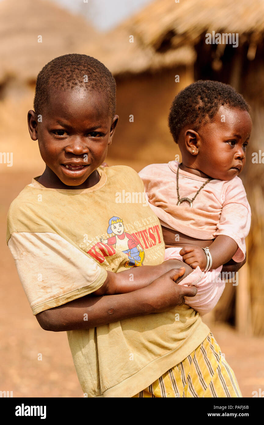 ACCRA, GHANA - MARCH 6, 2012: Unidentified Ghanaian boy holds his little brother on his hands in the street in Ghana. Children of Ghana suffer of pove - Stock Image