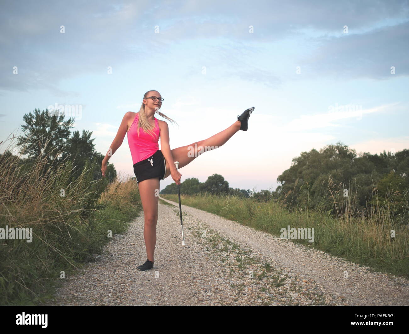Bespectacled Blonde Teen Majorette Girl Twirling Baton Outdoors in Workout Clothing - Stock Image