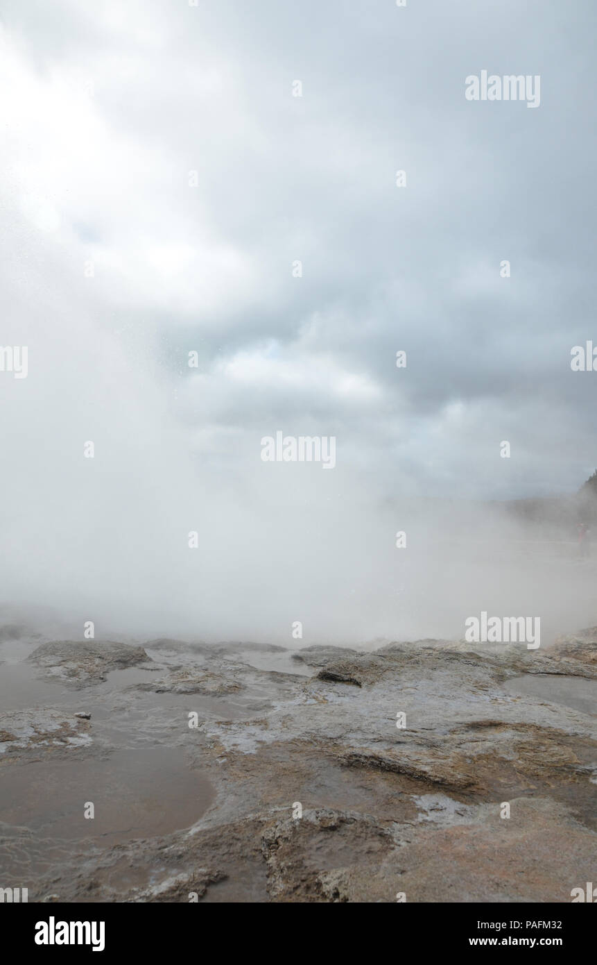 Blue sky breaking out of the clouds with a steaming geyser - Stock Image