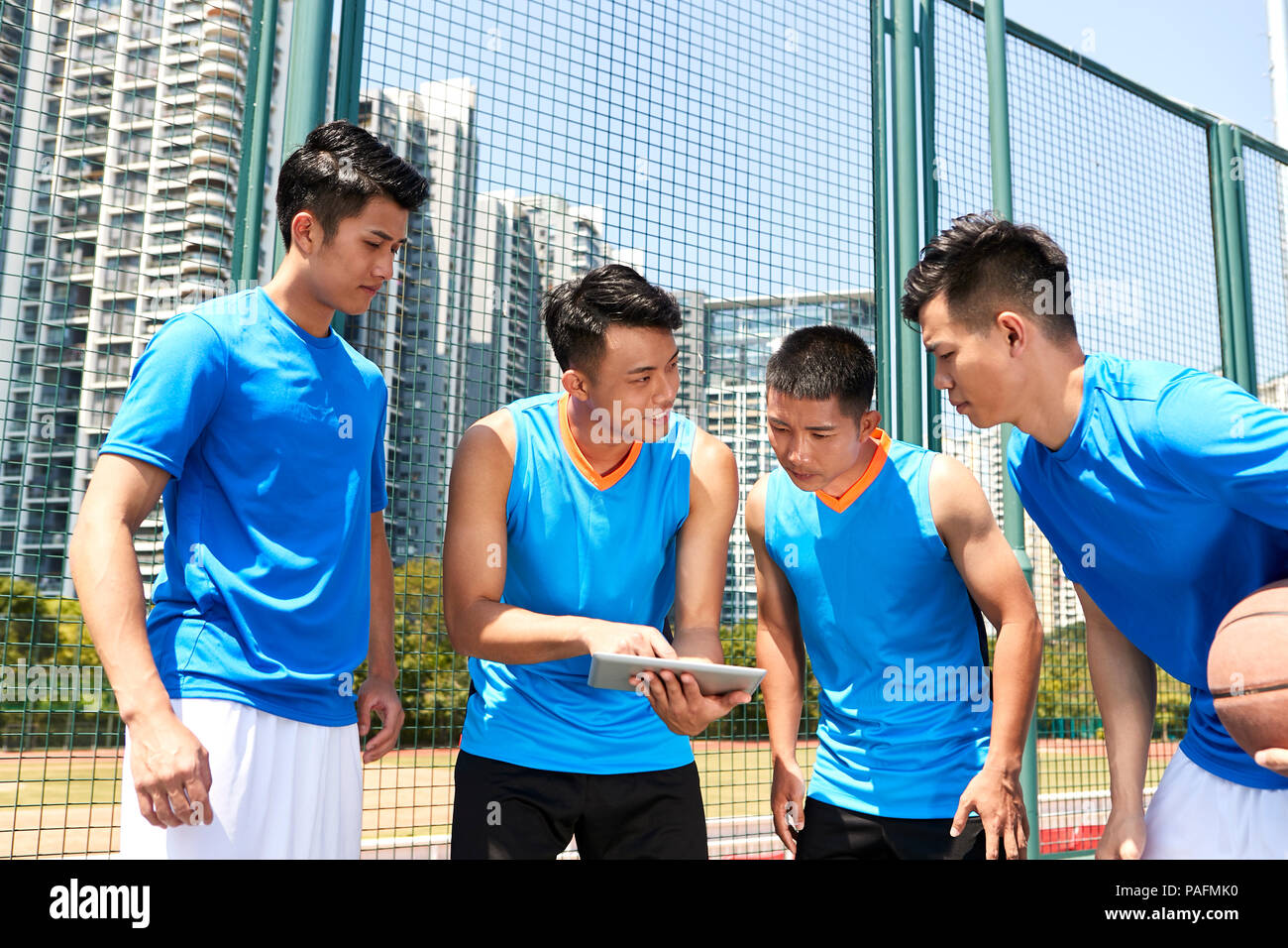 young asian basketball players discussing tactics using digital tablet at court side. - Stock Image