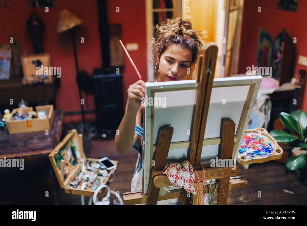 Indoor shot of professional female artist painting on canvas in studio with plants. - Stock Image