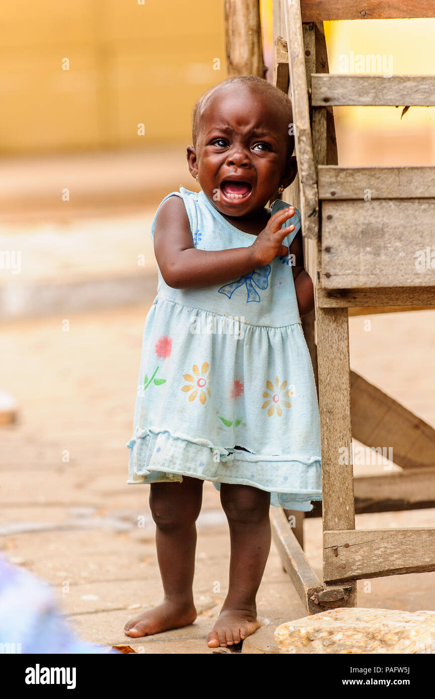 PORTO-NOVO, BENIN - MAR 10, 2012: Unidentified Beninese little girl in a blue dress cries loudly. People of Benin suffer of poverty due to the difficu - Stock Image