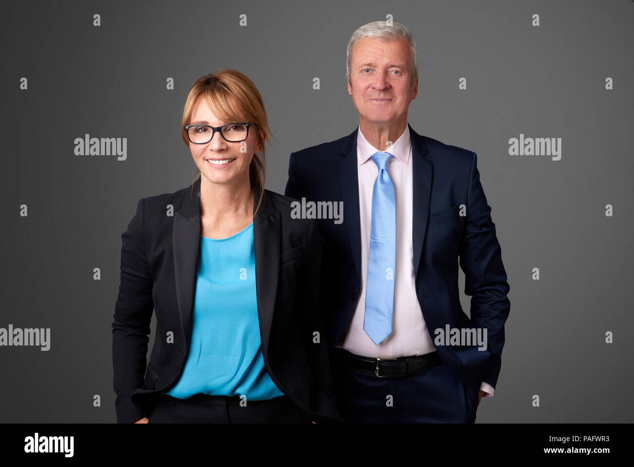 An attractive middle aged businesswoman and an exectuive professional man standing at isolated background. - Stock Image