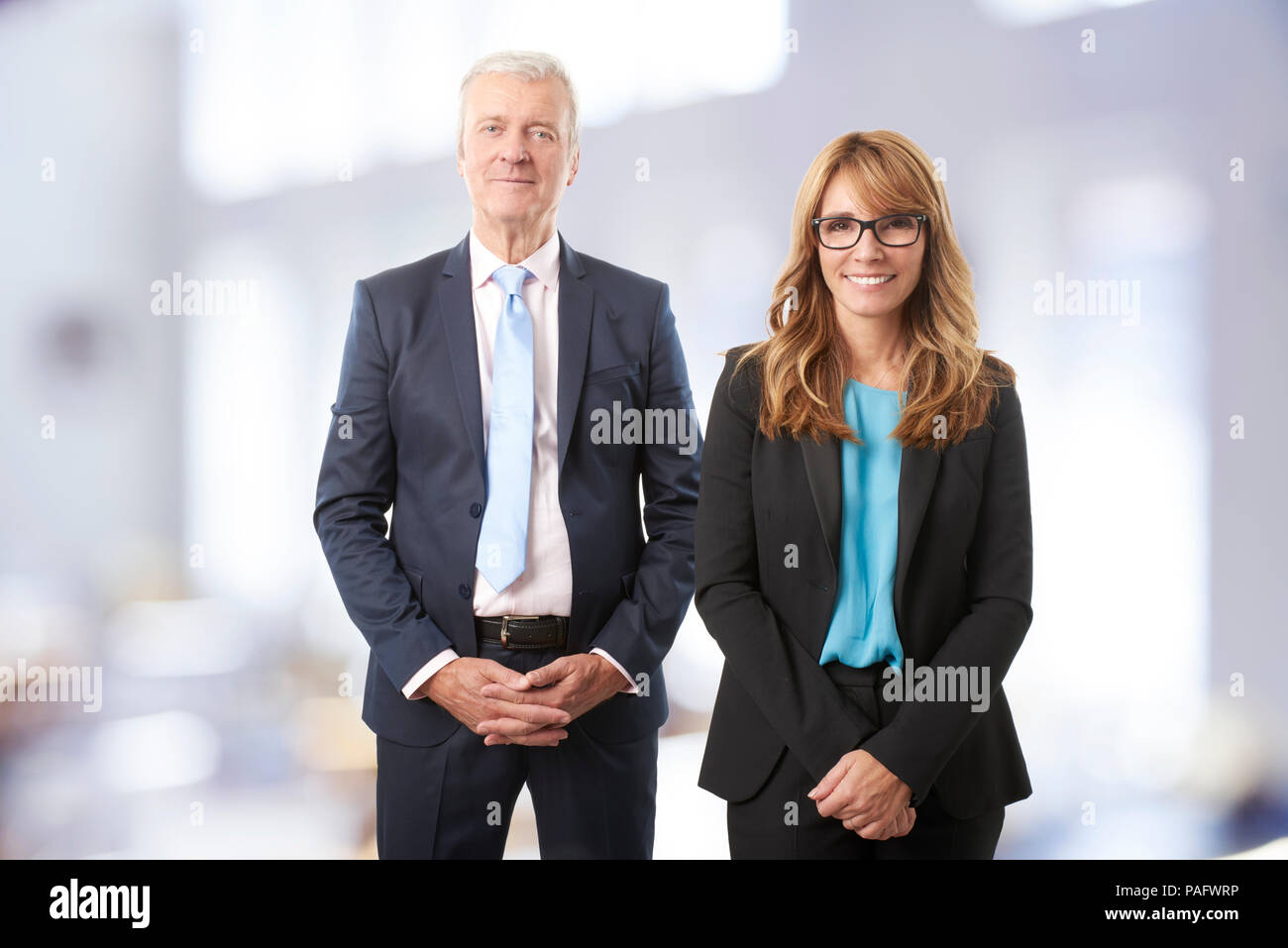 A successful business people standing in the boardroom after business meeting. Happy mature professional woman and a senior financial advisor looking  - Stock Image