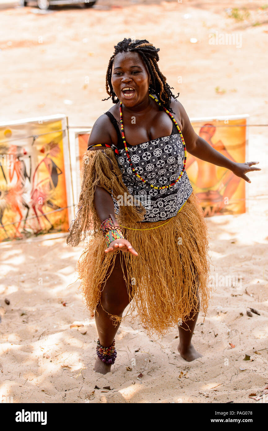ANGOLA, LUANDA - MARCH 4, 2013:  Angolan sympathic woman makes the street performance of the national falk dance in Angola, Mar 4, 2013. Music is one  - Stock Image