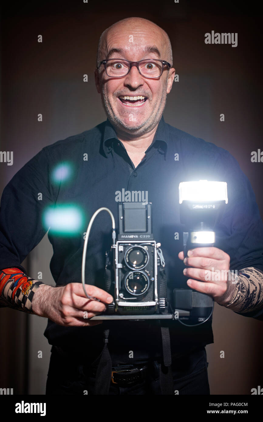 Selfportrait of photographer holding film camera Mamiya C220 with flash Metz 45CT-5. 45, 50, 55, 60 years old. Manhattan, New York City, USA - Stock Image