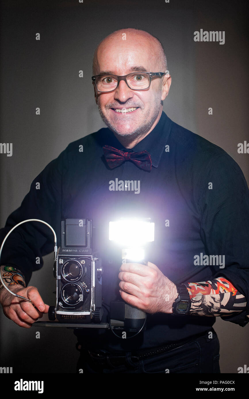 Selfportrait of photographer holding film camera Mamiya C220 with flash Metz 45CT-5. 45, 50, 55, 60 years old. - Stock Image