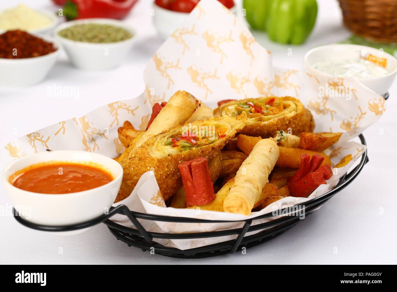 Mixed appetizer of french fries, fried sasusage, fried zucchini, pastry, sigara borek with sauces - Stock Image