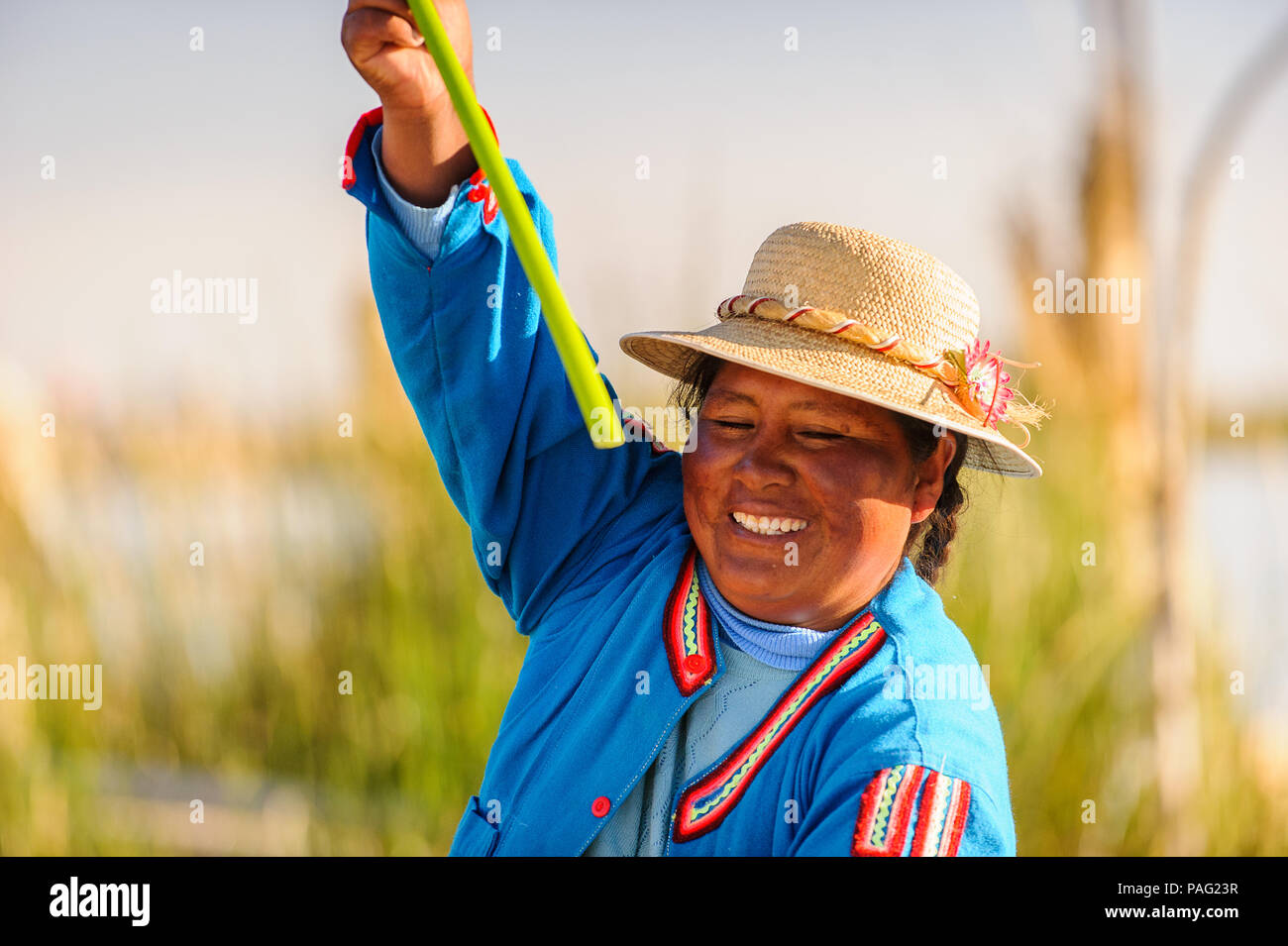 PUNO, PERU - NOVEMBER 7, 2010: Unidentified Peruvian woman in traditional clothes rows the boat in Uros Islands, Peru, Nov 7, 2010. Uros Islands iclud - Stock Image