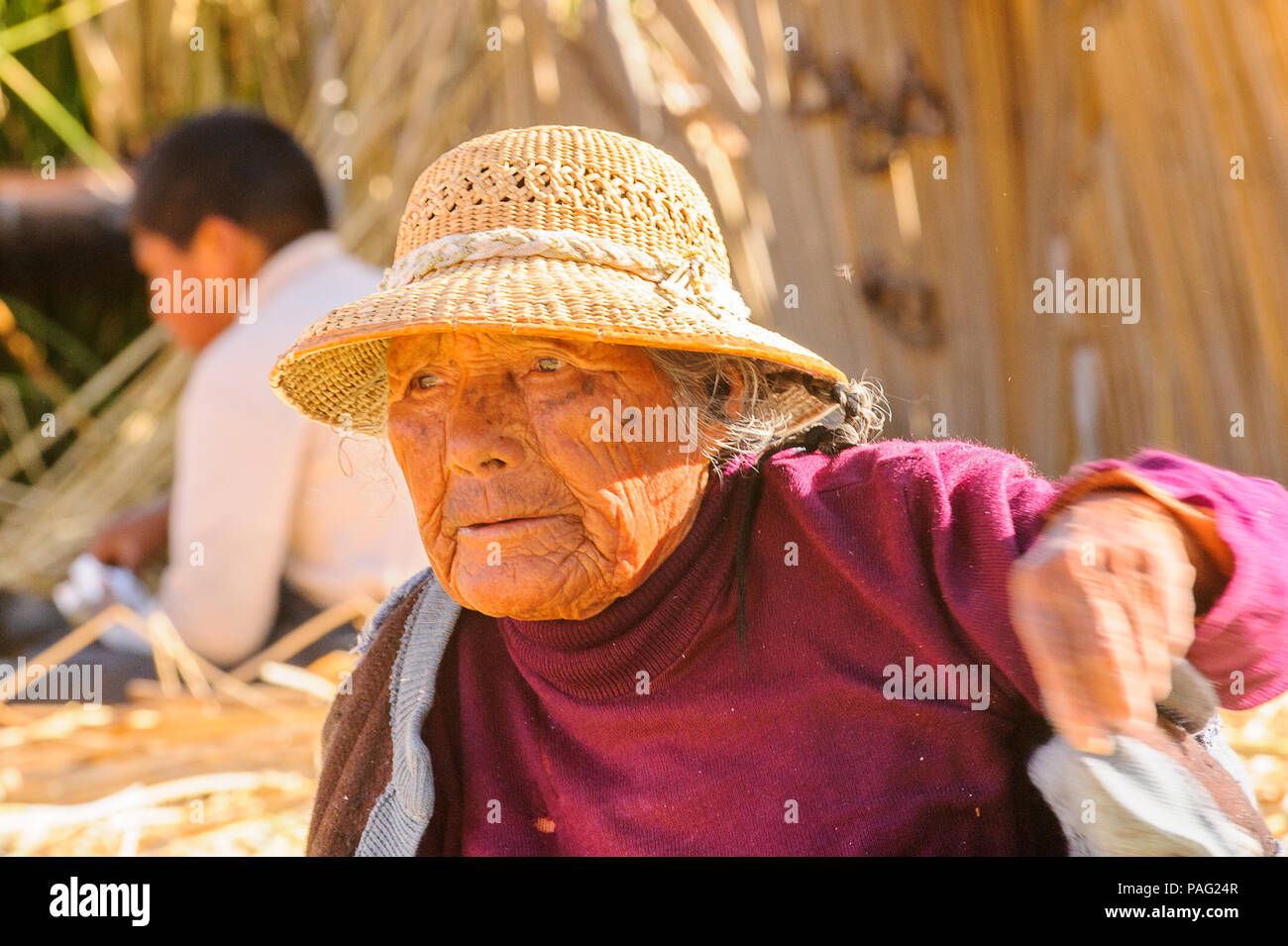 PUNO, PERU - NOVEMBER 7, 2010: Unidentified Uros woman in traditional clothes on the  Uros Islands, Peru, Nov 7, 2010. Uros Islands iclude 42 floating - Stock Image